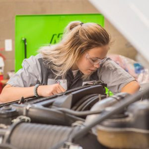 Female student working on automobile.